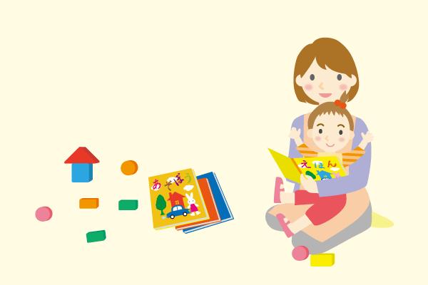 膝の上に座っている子どもに絵本を読んでいる様子